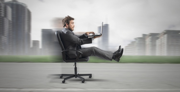 Man with laptop drives fast on office chair; Copyright:...