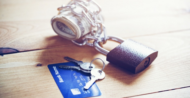 Banknotes secured by a lock and a credit card with keys; copyright:...