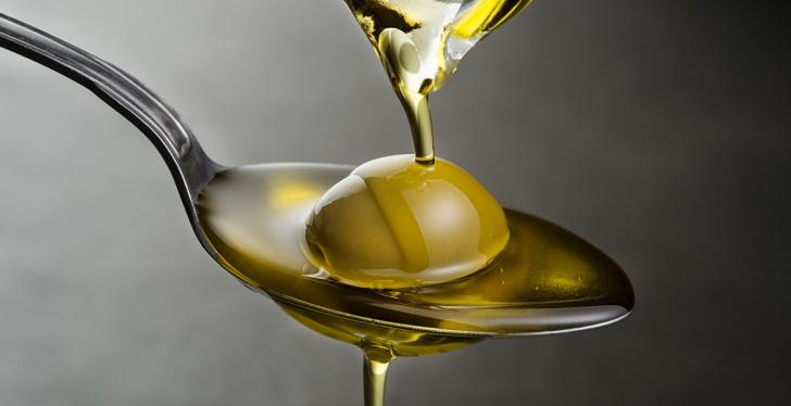 Olive oil trickling down onto a spoon with an olive on it; copyright:...
