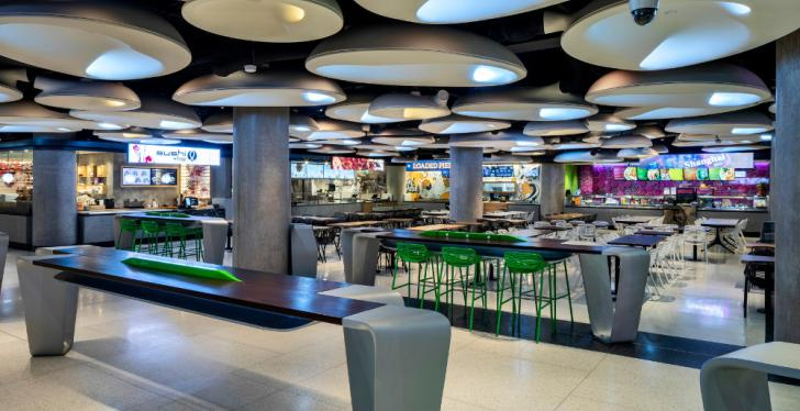 Empty food court with bars and tables and lighting installation at the ceiling;...