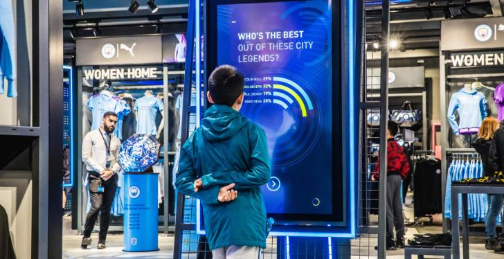 Boy standing in front of a digital screen in a sport's store; copyright:...