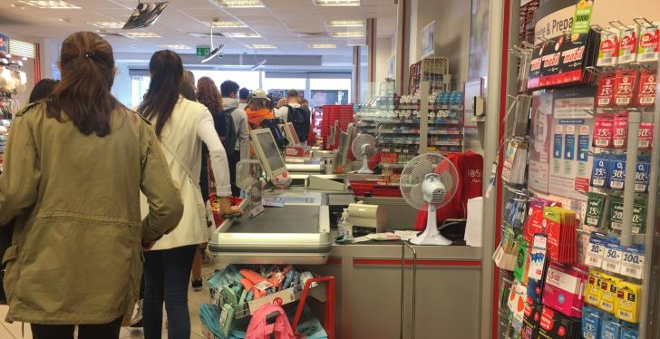 Customers waiting in a long line in a store at the checkout; copyright:...