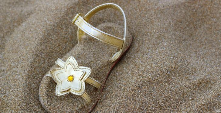Sandal with a decorative flower half buried in sand; copyright: Bildagentur...