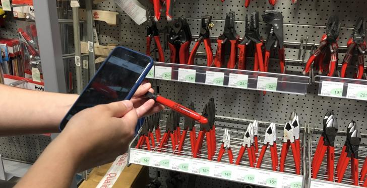 Person scans barcode on red pliers with a smartphone in a DIY market;...