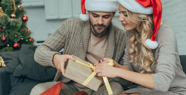 Young couple opens Christmas present