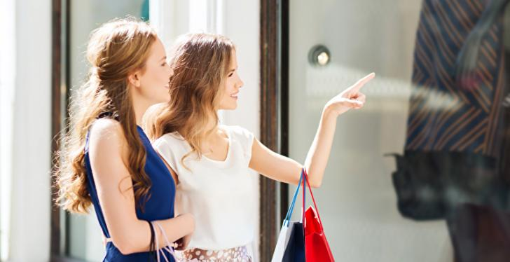 Two young women look into a shop window while shopping. A woman raises her hand...