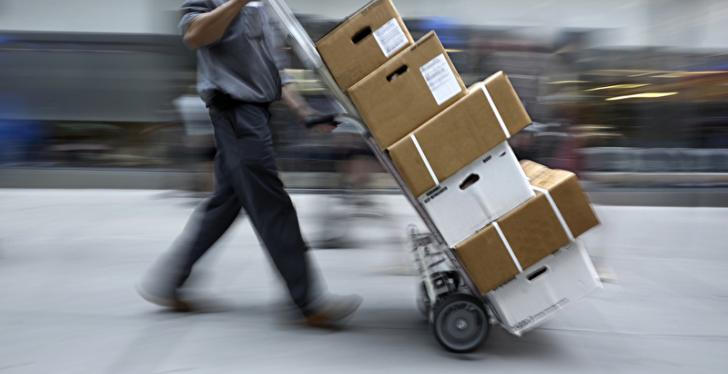 Man with sack truck loaded with parcels walks through a logistics center...