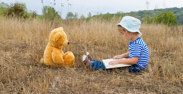 Small child sits with teddy bear and book in the grass and reads aloud...