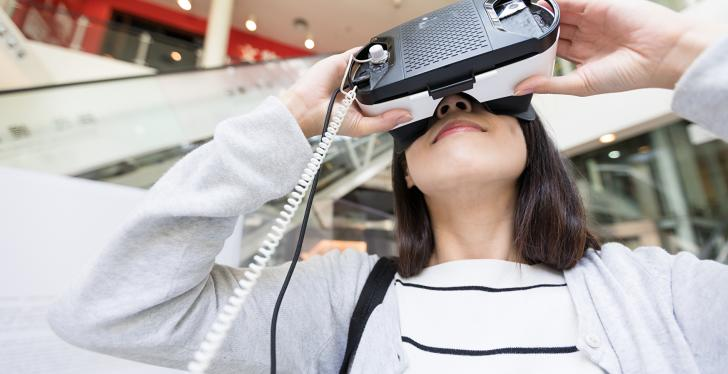 Woman with VR glasses in the shopping centre