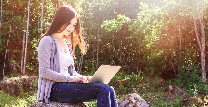 Young woman sitting on a rock, using a computer