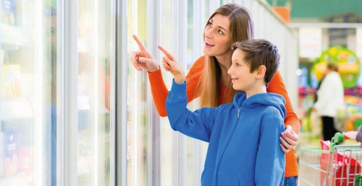 A mother and a boy point their fingers at a refrigerated shelf in a supermarket...