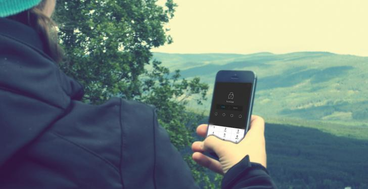 Person with view over wooded hills in outdoor clothing looks at smartphone...