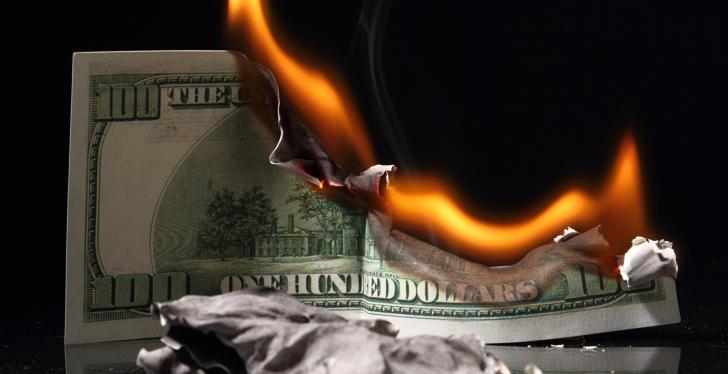 A burning dollar note; copyright: PantherMedia/v.gi...