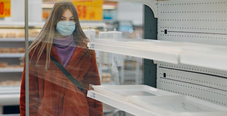 Woman with breathing mask stands in front of empty shelves in the supermarket...