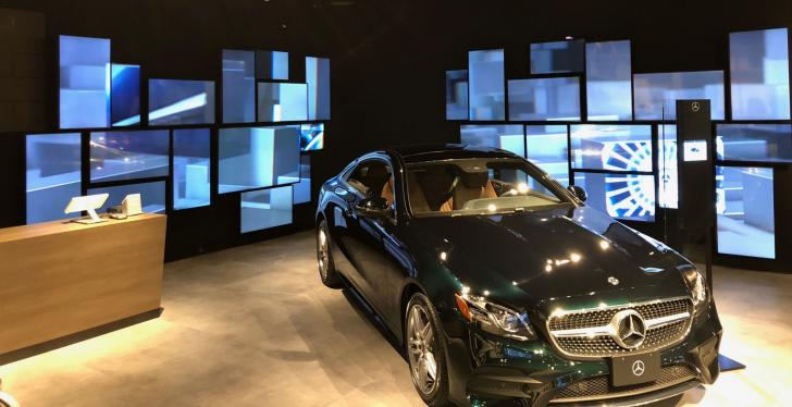 Many different digital signage screens in a showroom with a Mercedes...