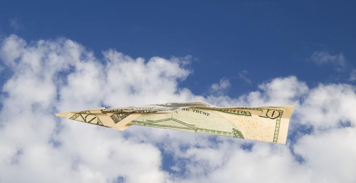A dollar note as a paper airplane flying through the cloudy sky...