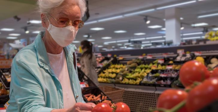 An elderly woman is looking at tomatoes in a supermarket, wearing a face mask...