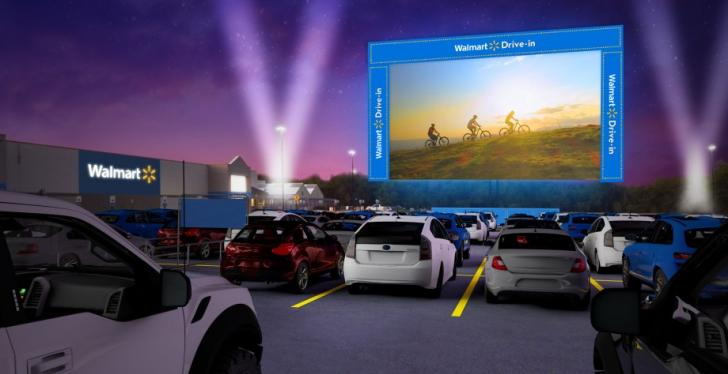 A screen and cars in a drive-in movie theater