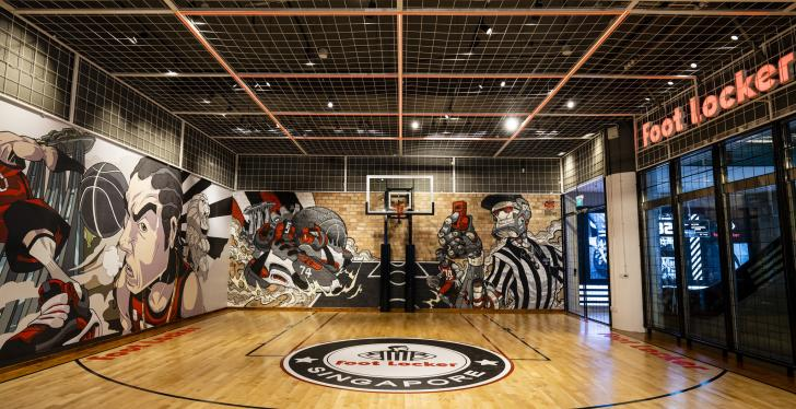 A basketball court with murals on the wall