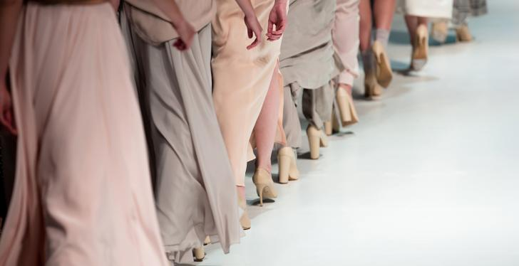 Models in dresses walking down a runway