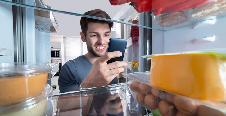 A young man looking into his fridge and holding a smartphone...