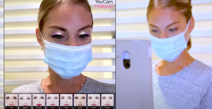 A woman with a face mask using a virtual makeup try on tool...