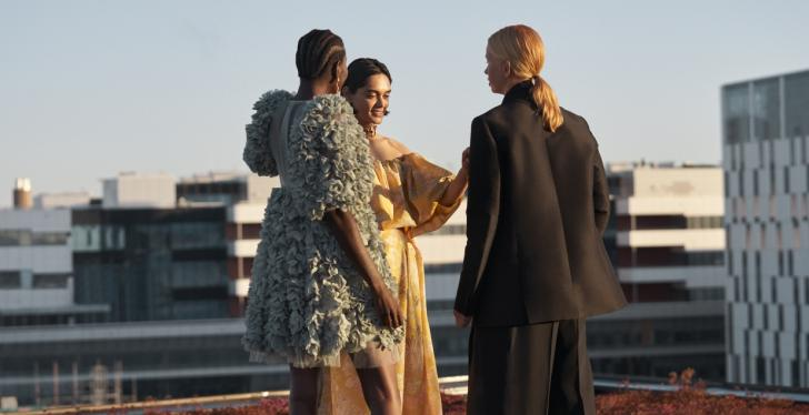 Three female models are standing on a roof top