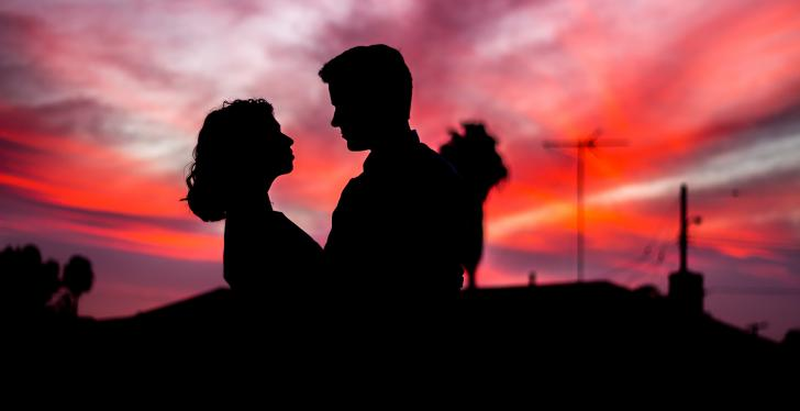 The dark silhouettes of a woman and a man in front of a red sunset; Travis...