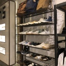 The shoe shelf consists of simple black wire mesh cages, which are mounted on...