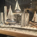 Small sailboats and glasses on sand in a shop window...