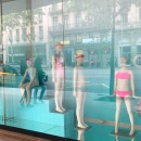 Four child mannequins in swimsuits in a shop window with blue background...