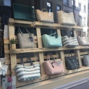 Shop window decoration with a wooden pallet with bags on it...