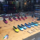 Colorful ladies shoes in a shop window on a wooden table...