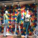 Three female mannequins in front of a wall of colored pinwheels in a shop window...