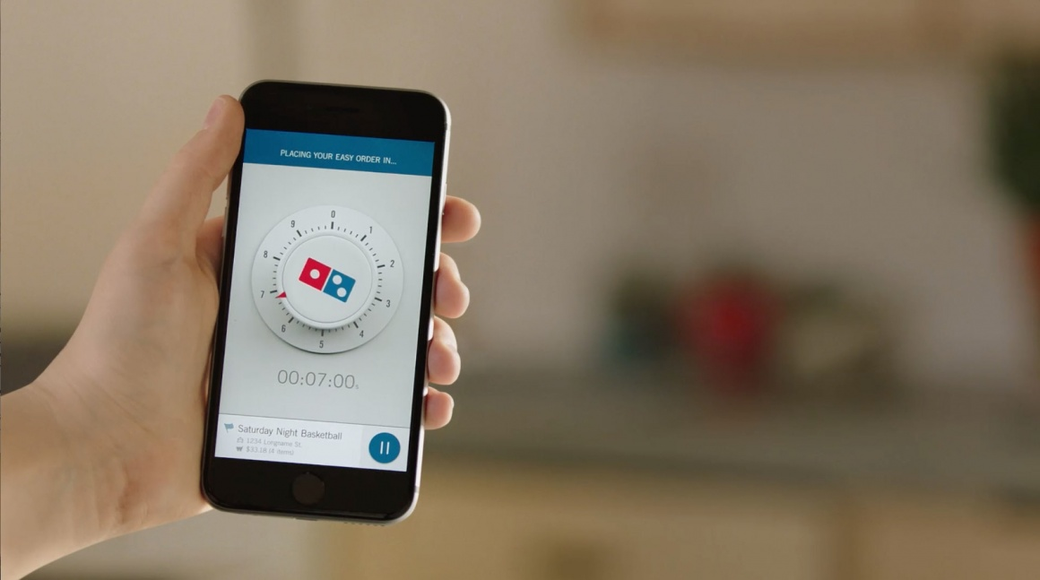 Photo: Hand holding smartphone with Dominos Zero Click Ordering App on display;...