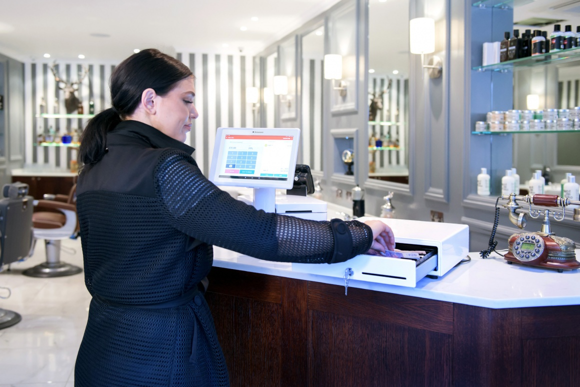 Photo: Woman handling the cash drawer on the counter of a hair salon;...