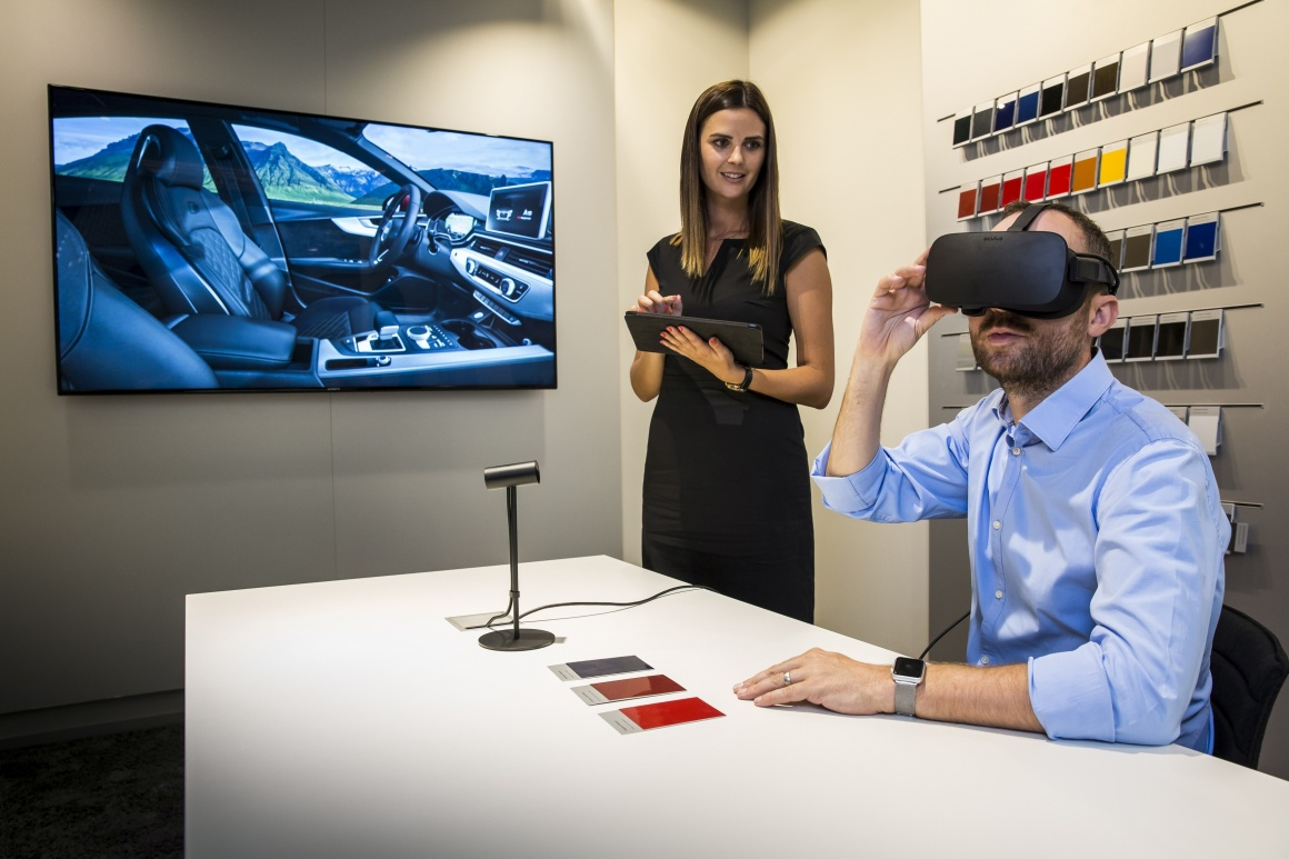 Customer with VR glasses in front of screen with interior car design;...