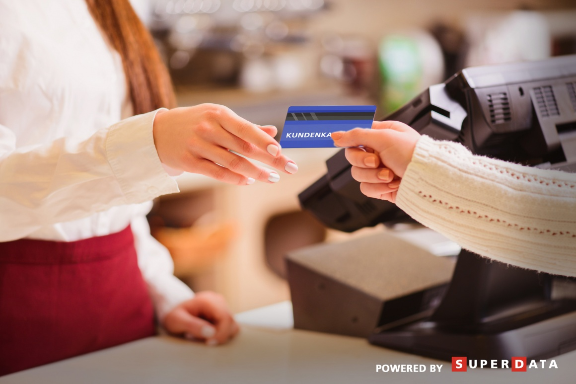 Customer hands over customer card to cashier; copyright: Superdata...