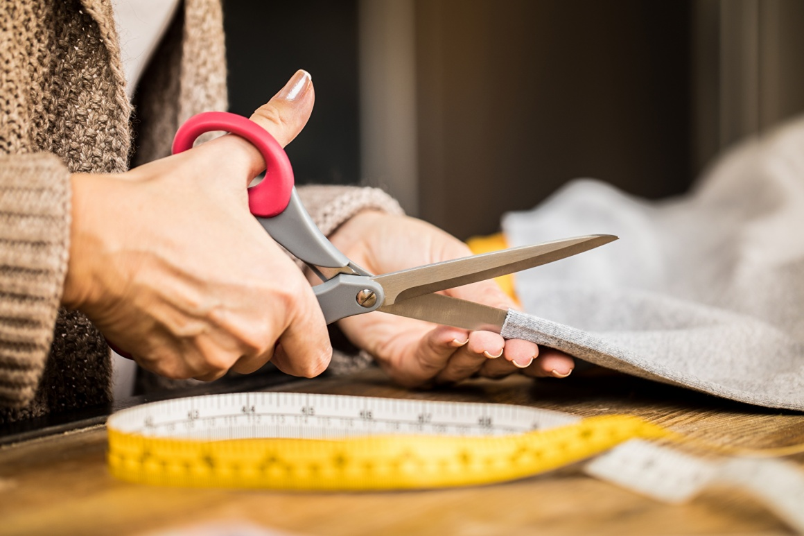 Tailor cutting fabric and measuring tape on the table; copyright:...