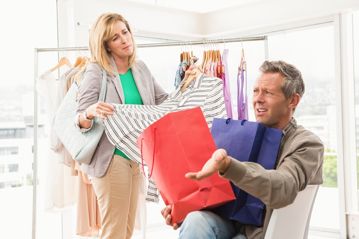 A woman is looking at clothes on a bar, a man sits angry with shopping bags in...