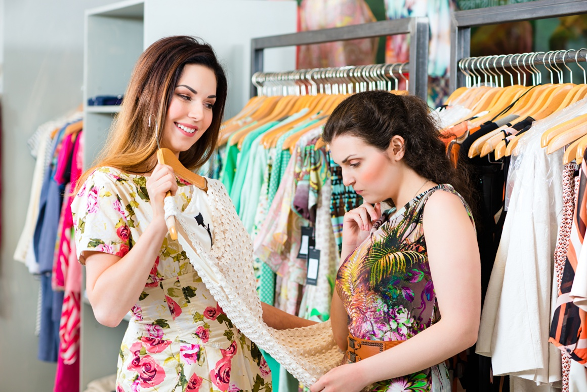 Two women looking at a dress in a shop, one enthusiastic, one sceptical;...