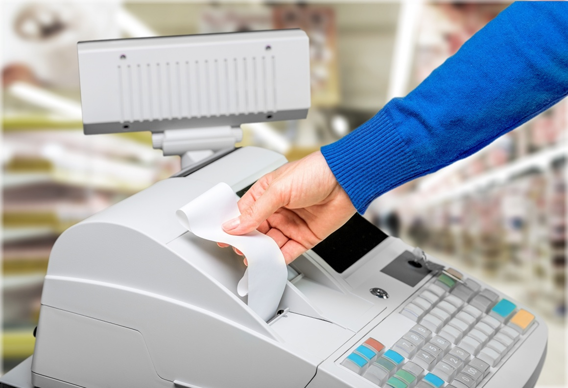 Hand reaches for receipt, which is printed from the cash register....