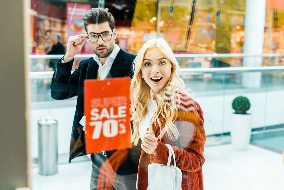 Man and woman look into a shop window with a sell sign....