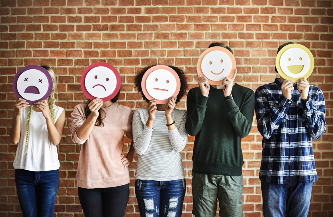 Five people stand in a row and hold smileys in front of their faces....