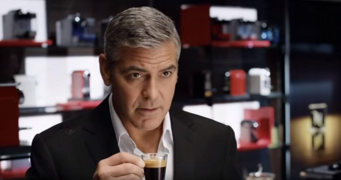 Actor George Clooney drinking espresso from a glass cup; screenshot of a...