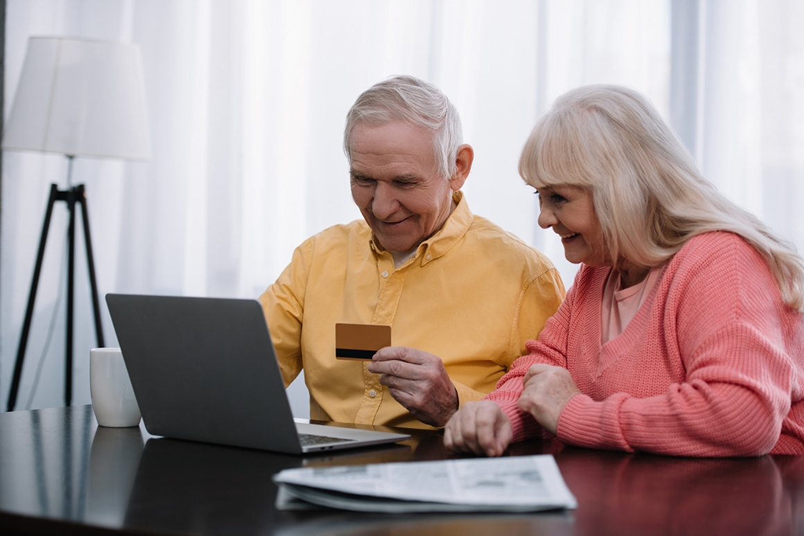 Two seniors - man and woman - sitting in front of their laptop and shopping...