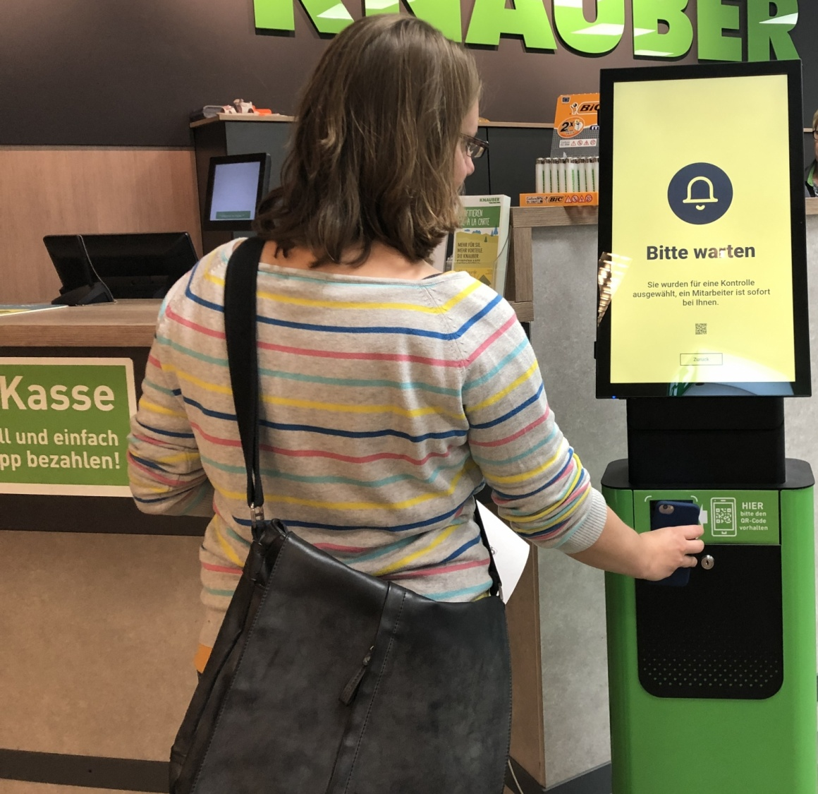 Woman holds smartphone to a digital stand in a store; copyright: iXtenso/Laska...