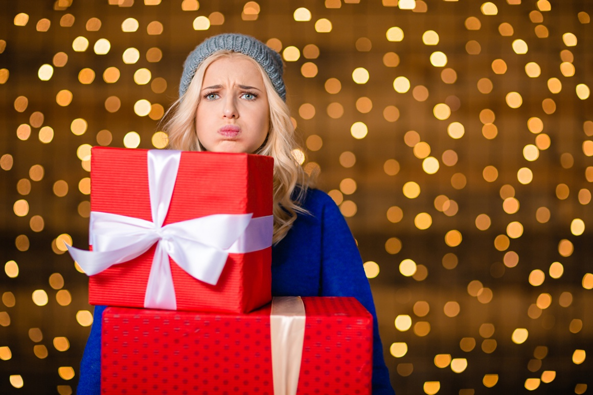 Woman looking unhappy, holding to big wrapped gift boxes under her chin with...