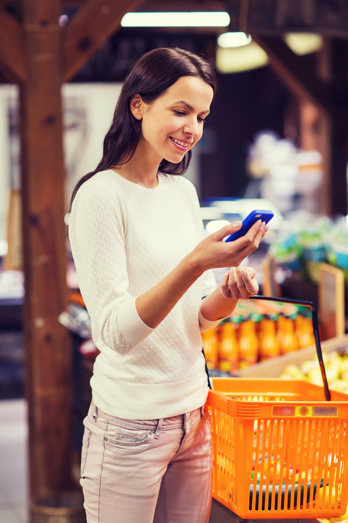 Woman with shopping basket in grocery store, holding her smartphone in her hand...