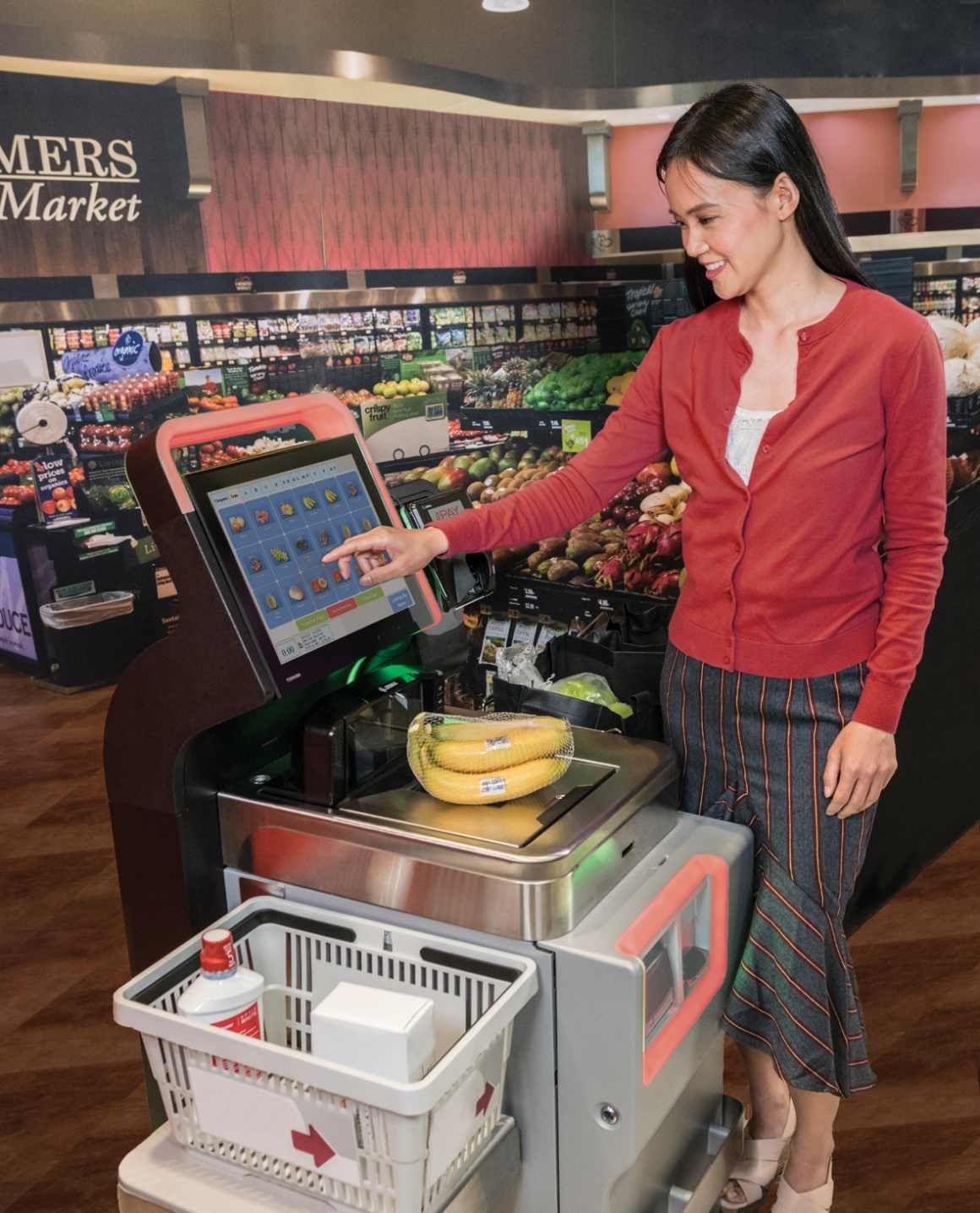 A woman is standing at a self-service checkout in the supermarket and typing on...